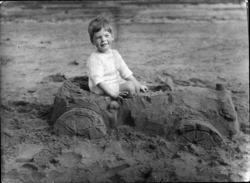 Doug on a beach in a sandcastle car.
