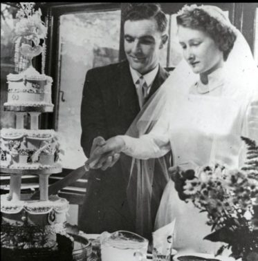 Margaret and Dig cutting their wedding cake.