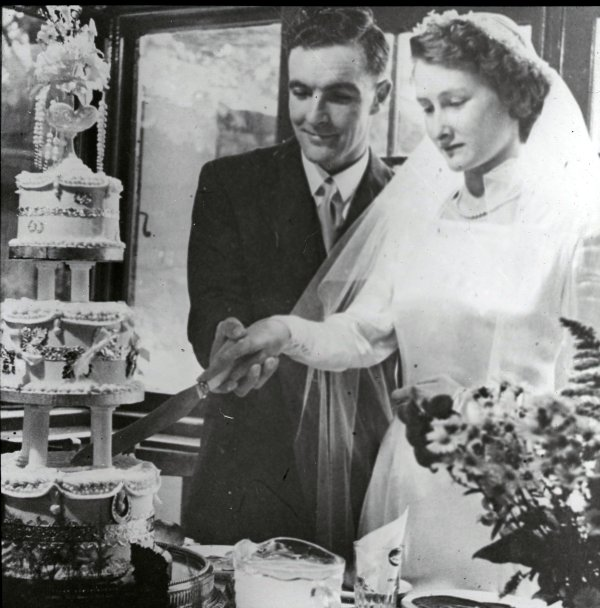 Margaret and Dig (William Last) cut the cake at their wedding reception.